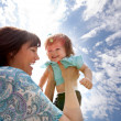 Stock Photo: Mother Holding Daughter in Air