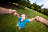 Father Spinning Son Outdoors in Park — Stock Photo