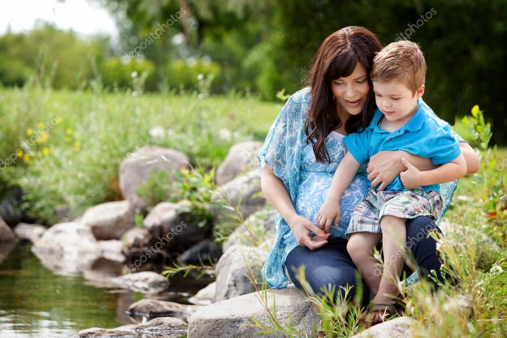 Happy portrait of a mother and son playing by a lake in a park — Stock Photo #12660428