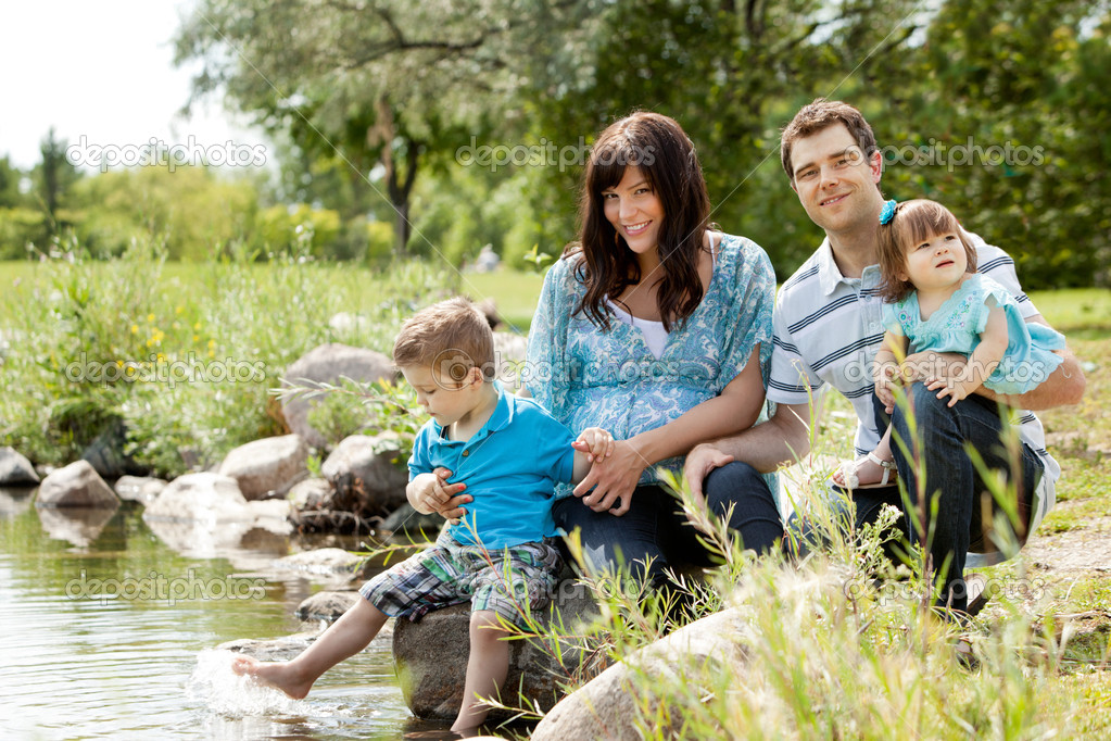 Happy similing young family sitting by lake  Stock Photo #12660595