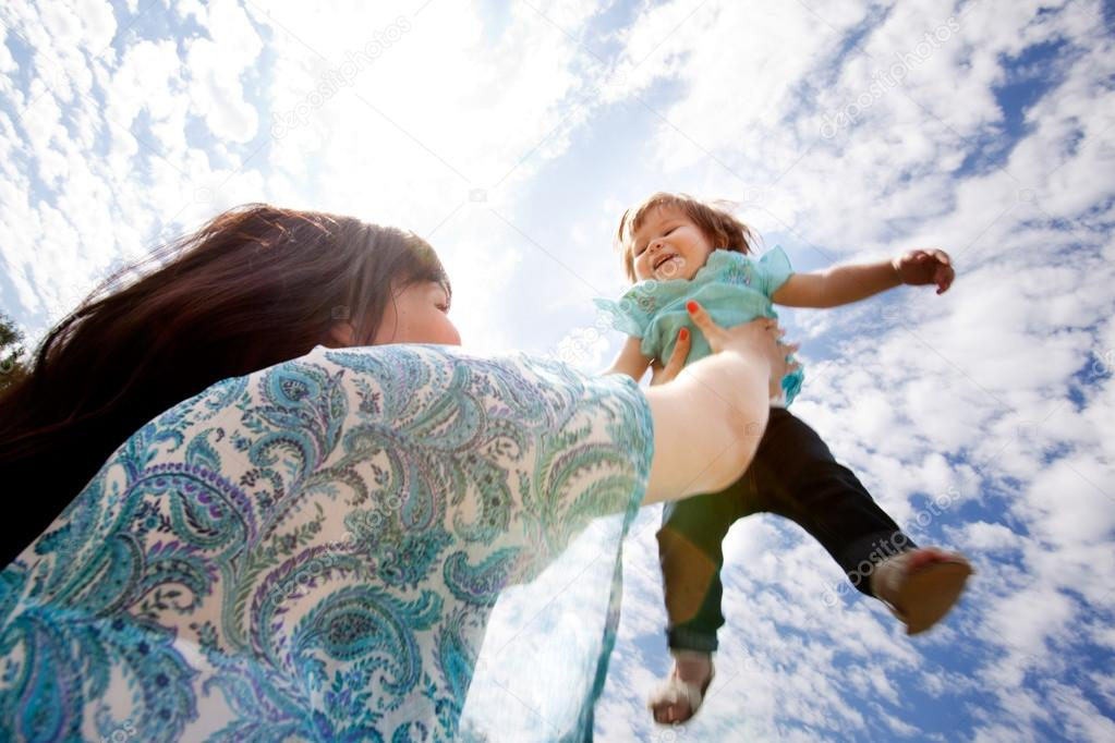 Happy exciting young daughter being thrown into sky by mother — Stock Photo #12673133