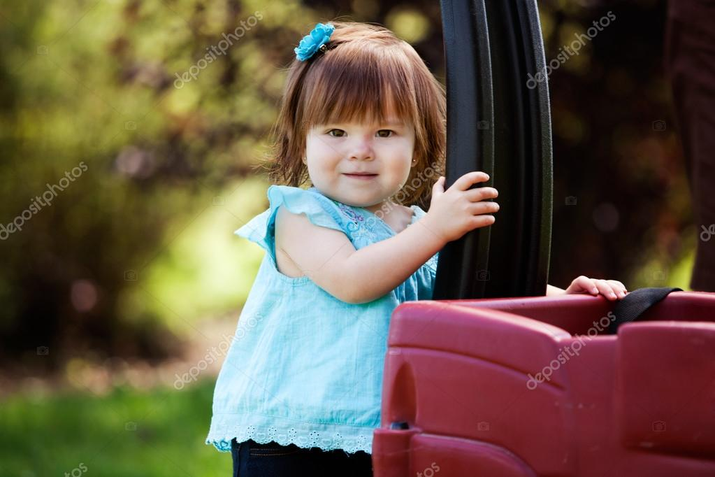 Portrait of an adorable young girl outdoor in park with wagon — Stock Photo #12675560
