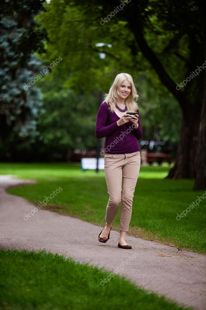 Woman in park looking at camera using cell phone — Stock Photo #12746807