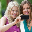 Female Friends Photographing Themselves - Stock Photo