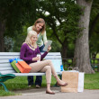 Women With Shopping Bags Using Tablet PC At Park — Stock Photo