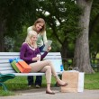 Women With Shopping Bags Using Tablet PC At Park - Stock Photo