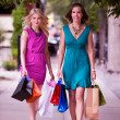 Two Women Walking Down Street - Stock Photo