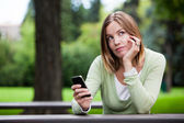 Thoughtful Woman holding Cell Phone — Stock Photo