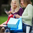 Women With Shopping Bags Using Tablet PC Outdoors — Stock Photo