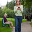 Woman Reading Text Message In Park — Stock Photo