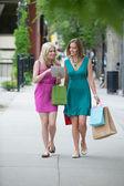 Koleżanki z torby na zakupy przy użyciu cyfrowego tabletu — Zdjęcie stockowe