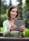 Woman in Park with Digital Tablet — Stock Photo