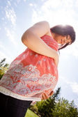 Pregnant Woman in Park Looking at Belly — Stock Photo