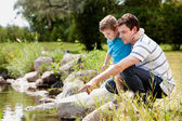 Fashing and Son Playing Near Lake — Stock Photo