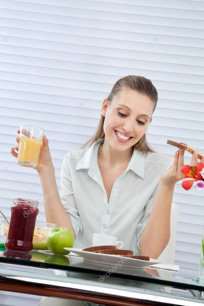 Happy young woman looking down at plate of bread slices while having orange juice — Stock Photo #12807599