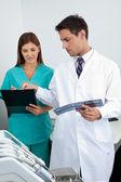 Asistente analizar informe del paciente y médico — Foto de Stock