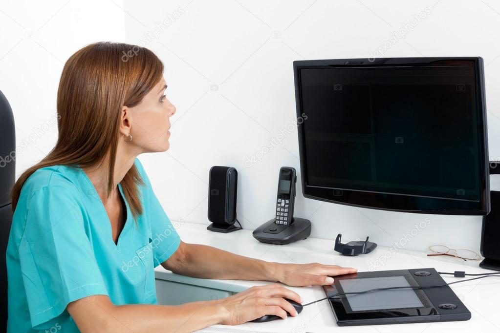 Female dentist using computer at office desk — Stock Photo #13038185