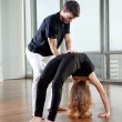 Instructor Adjusting Woman's Yoga Posture - Stock Photo