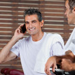 Man On Call While Friend Looking At Him In Health Club - Stock Photo