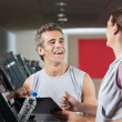 Stock Photo: Happy Instructor Looking At Female Client Exercising On Treadmil