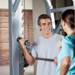 Man Lifting Weights While Looking At Instructor — Stock Photo #13056985