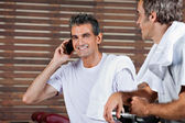 Man On Call While Friend Looking At Him In Health Club — Stock Photo