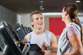 Happy Instructor Looking At Female Client Exercising On Treadmil — Stock Photo