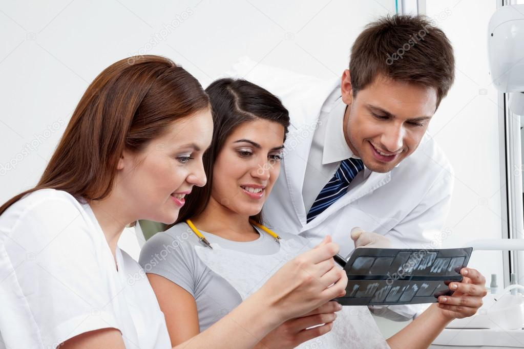 Female nurse and dentist explaining X-ray report to patient with doctor in the background — Stock Photo #13050380
