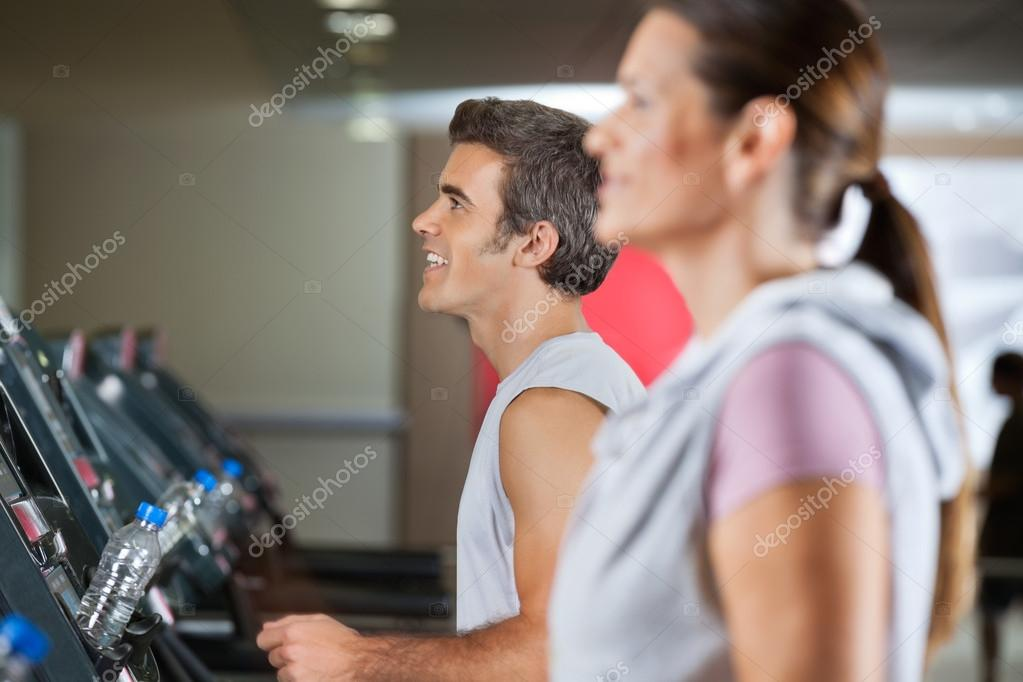 Side view of happy young man and woman running on treadmill in health club — Stock Photo #13061402
