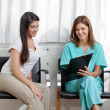 Dentist And Patient Looking At Clipboard - Stockfoto