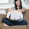 Pregnant Woman Holding Baby Clothing On Sofa — Stock Photo #13133257