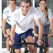 Men And Woman On Spinning Bikes — Stock Photo