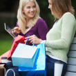 Women With Shopping Bags Using Tablet PC Outdoors — Stock Photo #13134440