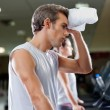 Man Wiping Sweat With Towel At Health Club - Stock Photo