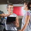 Stock Photo: Happy Instructor Looking At Client Exercising On Treadmill
