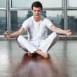 Young Man Meditating On Wooden Floor — Stock Photo #13134835
