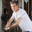 Mature Man Working Out In Fitness Center - Stock Photo