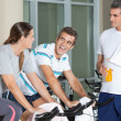 Man Looking At Happy Friends Exercising On Spinning Bike — Stock Photo #13136267