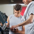 Instructor Making Notes While Standing Besides Man On Treadmill — Stock Photo #13136979