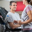 Instructor Looking At Female Client Exercising On Treadmill — Stock Photo