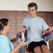 Man Using An Exercise Machine While Looking At Instructor — Stock Photo