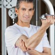 Stock Photo: Mature Man Working Out In Fitness Center