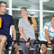 Man Looking At Friends With Juice Bottles On Spinning Bike — Stock Photo