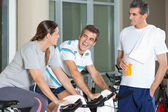 Man Looking At Happy Friends Exercising On Spinning Bike — Stock Photo
