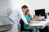 Dentist With Assistant Analyzing Report — Stock Photo