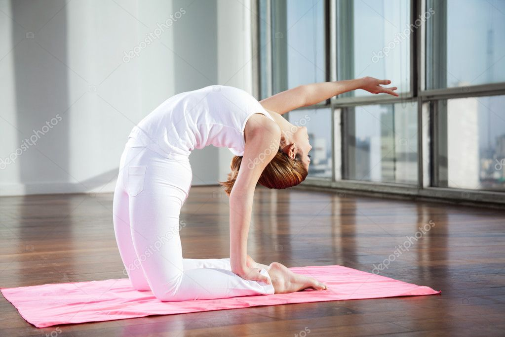 Full length of a young woman practicing yoga in Camel position on mat — Stock Photo #13135383
