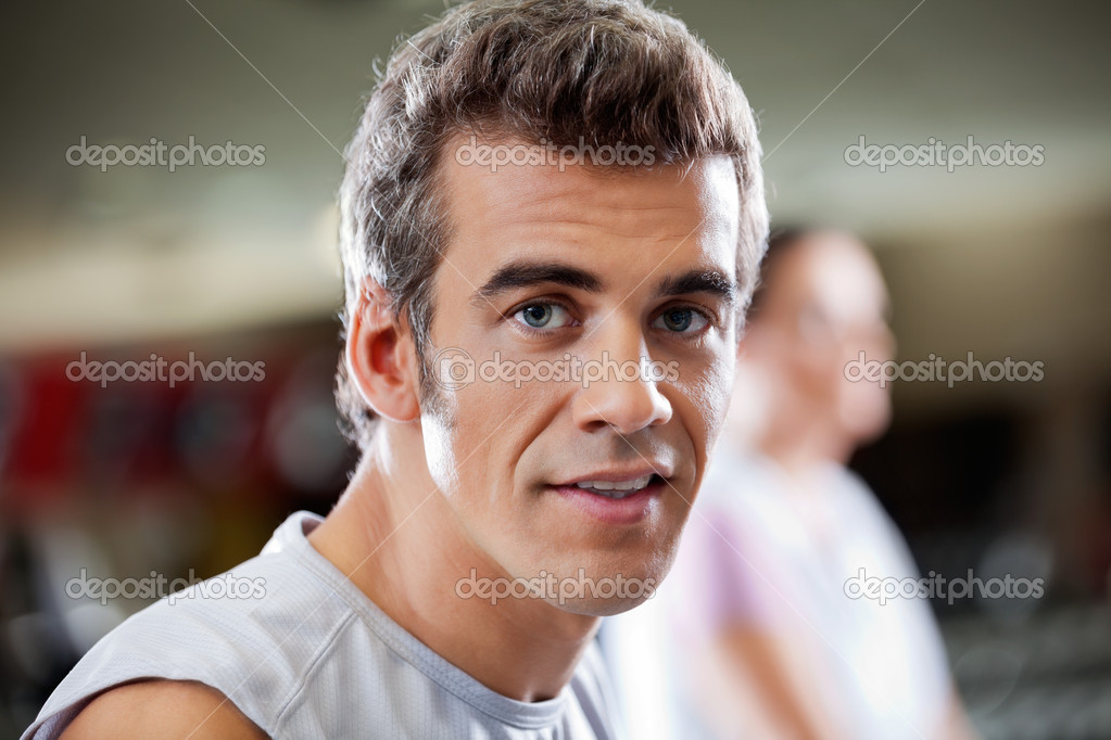 Close-up portrait of young man in health club with woman in the background — Stock Photo #13136818