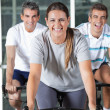 Stock Photo: Men And Woman On Exercise Bikes