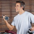 Man Lifting Dumbbell In Health Center - Stock Photo