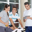 Friends Using Digital Tablet In Gym - Stock Photo
